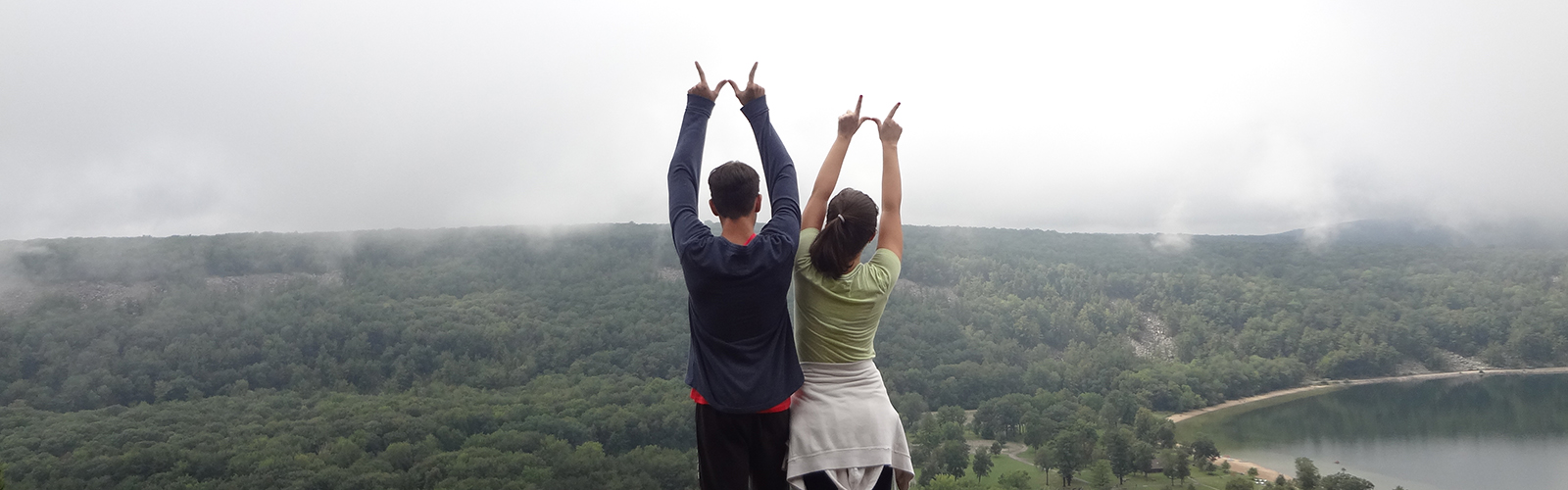 VISP students make the sign of 'W' while overlooking a scenic view.