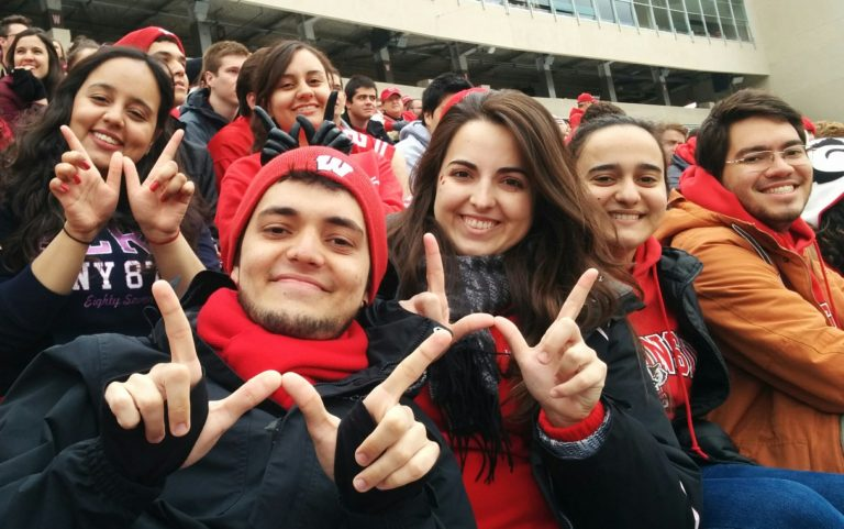 VISP students dressed in red and white make the 'W' sign with their hands at a Badger home game.